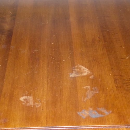 This table was damaged when a rag with some solvent based solution burned through the finish and into the wood.