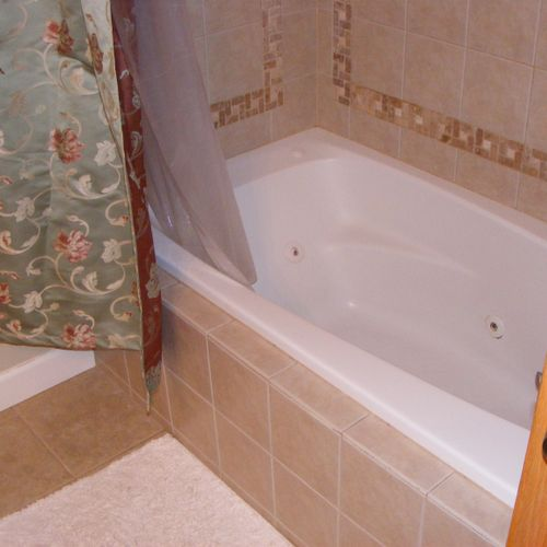 8 jet whirlpool tub, custom mosaic tiling, knee wall built to support tub, & entire bathroom covered in porcelain tile from wall to wall. Absolutely gorgeous!