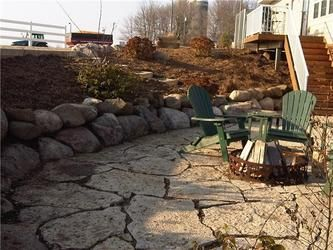 Flagstone patio with mulch and flower beds surrounding it.