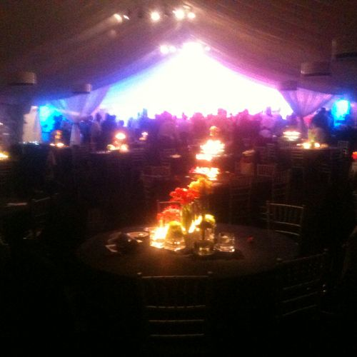 Tent lighting for dinning and dance, notice how centerpieces are illuminated in dinning and dancing area was a brillant lighting show.