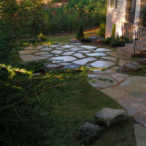 Natural stone pathways and patio, with boulders and beautiful plants and trees. Who wants to go inside?