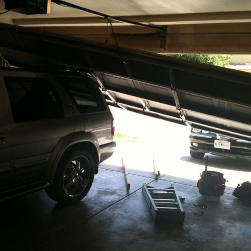 Our customer here closed the door onto the vehicle and the door came down on the car.  Luckily they had a little snowboard rack on top and the car did not get damaged.  1A Advanced Garage Doors came out here and put the door back on track and they were back in business in no time.