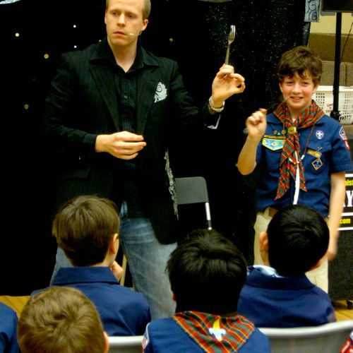 Eddy Ray performing a metal bending illusion during a cub scout banquet.