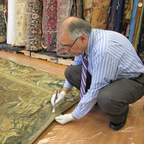 Dr. Khosrow Sobhe (Dr. Kay) inspecting a 200-year old antique French tapestry