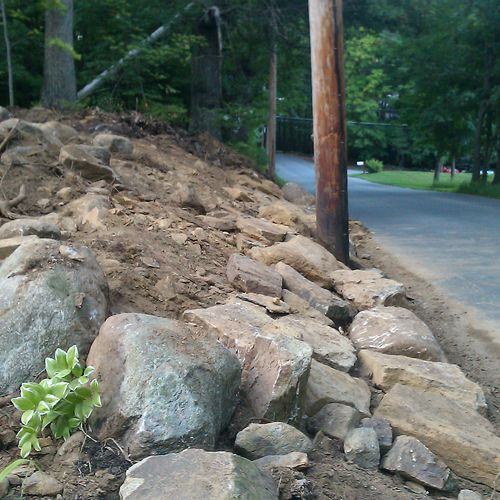 Lowered hill to create a view of on coming cars when pulling out of the driveway.