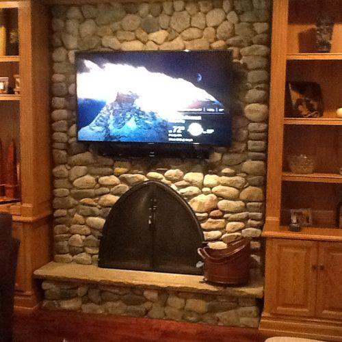 TV Wall Mount Installation over a rock fireplace with wires concealed in the wall