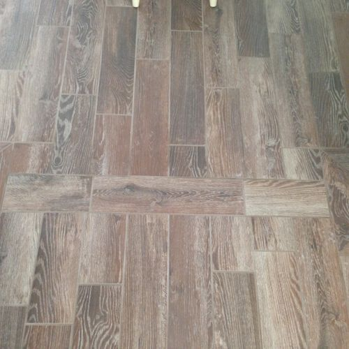 Beautiful, wood-look tile floor installed in Dining Room and Living Room (Transition between rooms shown in picture)