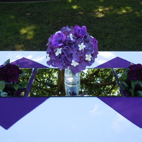 Bride's bouquet of Stephanotis with pearls in the centers. Purple hydrangea and purple anemonies. On each side there is a small centerpiece made of darker carnations and ruscus with butterflies.  All of these purple arrangements were either placed on a purple linen napkin or mirror square to add elegance.