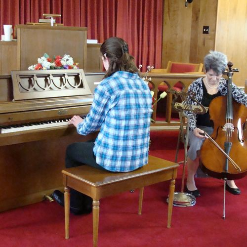 A piano student and a cello student warming up for the recital.