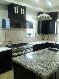 Interior Custom Kitchen design with white/gray granite, designer stainless steel stove, and dark stain solid wood cabinets.