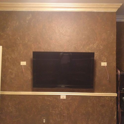 Custom faux crown molding and chair rails, mounted 55'' TV, and hidden speaker wire for surround sound and hidden power outlet
