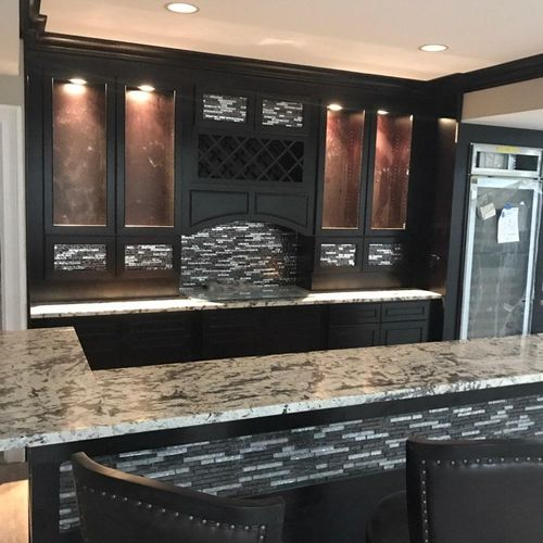 Glass tile in this bar sets off the espresso cabinets.