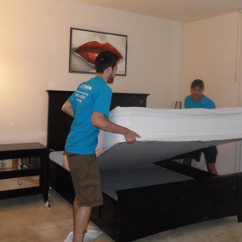 Jose and Eric disassemble a bed with ultimate care