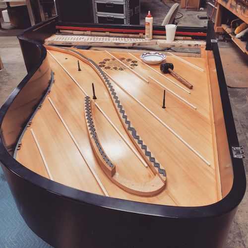 This is a complete rebuild on a Steinway Grand. Here we are repairing cracks in the soundboard.