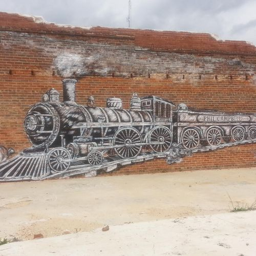 Sketch-style mural of train painted on side of historical building in downtown Phil Campbell.