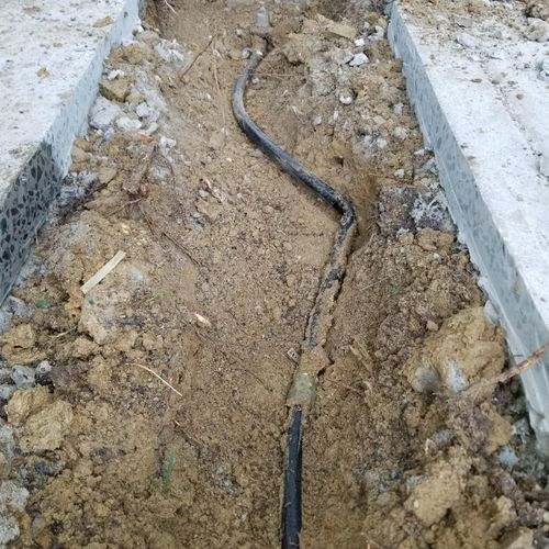 Kinked pipe split under sidewalk (before repair)