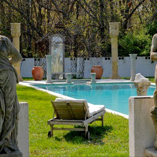 An exotic pool and jacuzzi graced with roses and ancient greek statues ..