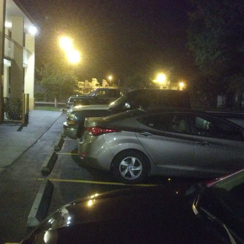 Cheating spouse vehicle (grey) located at night in hotel parking lot .