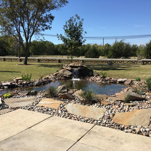 Koi pond with boulders and river rock and large water feature.