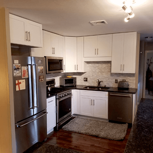 We installed white cabinets, w/ granite top & glass mosaic backsplash. We also installed beautiful Maple hardwood flooring, as well crown & baseboard
