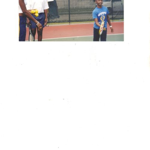 A young student learns to play tennis while I and Venus looks on.