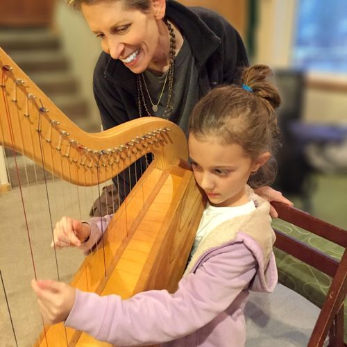 Anne Roos teaching harp lessons to 7-year-old student