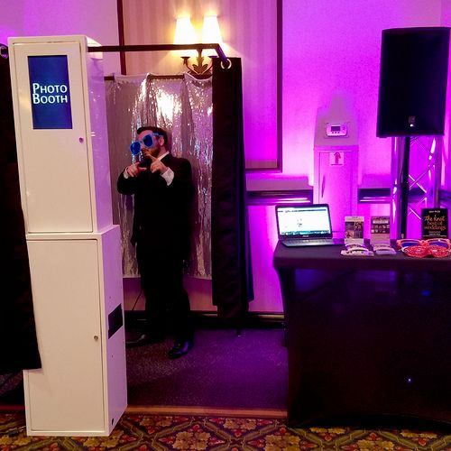 A visual of our photo booth with a silver sequin backdrop. All rentals come standard with a black curtain enclosure for privacy, but you may choose to use it as an open-air booth.