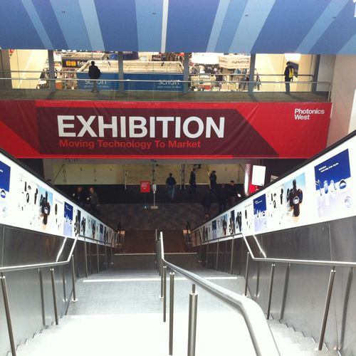 Large format graphics for Escalator Ads at a trade show for Rochester Precision Optics.