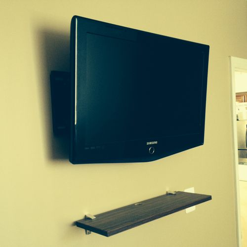 Wall-mounted TV and shelf for cable box.  Saves space and looks great.