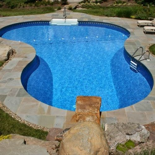Liner pool with blue stone patio and dive rock