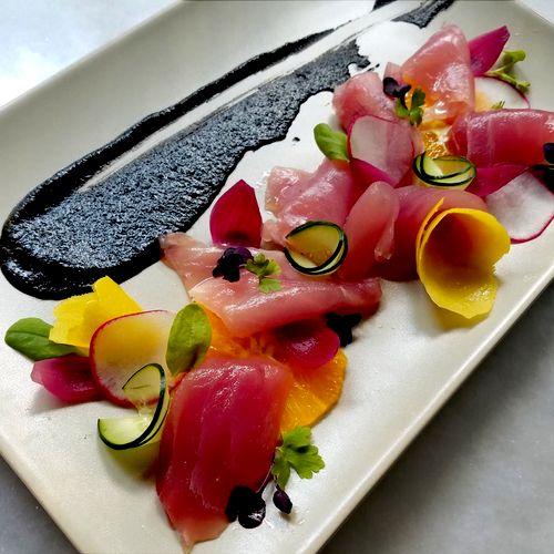 Tombo Tuna Crudo with Black Sesame Purée, Lemon Peel Confit, Pickled Red Pearl Onions, Lemon Oil, Cucumbers, Orange, Radishes, Shiso Leaves.