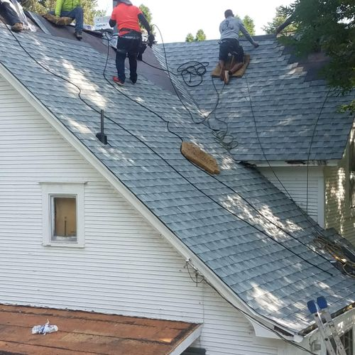 One of the original houses in Swisher: west elevation, crew completing Birchwood Timberline HD shingle installation