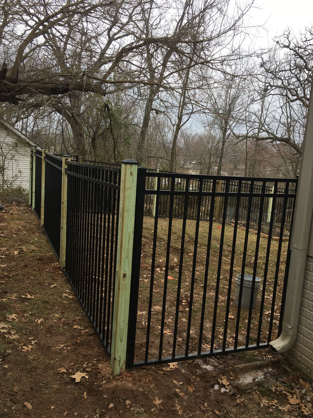 Ornamental metal fence with wood posts