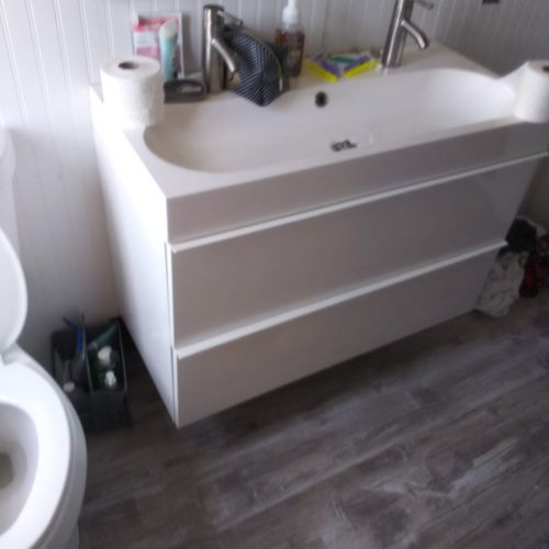 Installation of all new toilet, mirror, sink/2 drawer cabinetry, tub/shower liner, vinyl flooring and vanity light fixture