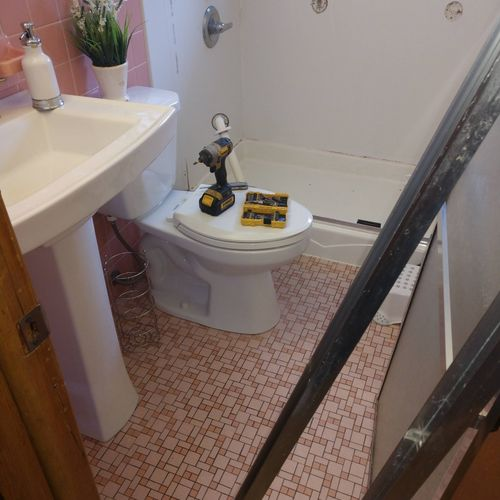 Bathroom with pink tile and walk-in shower with plastic shower walls and moldy drywall behind them. Time for an upgrade!