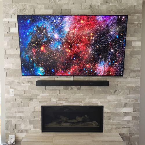 TV and Soundbar mounted on stone wall.