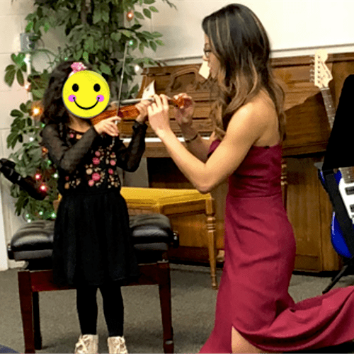 Helping out beginner violinist during her performance
