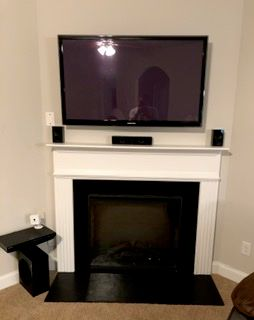 TV mounting over fireplace with surround sound system