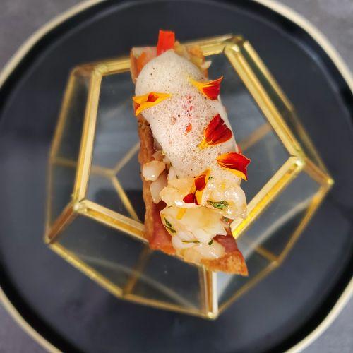 Pickled shrimp in muffuletta on top of fresh pork crackling topped with chard serrano foam.
