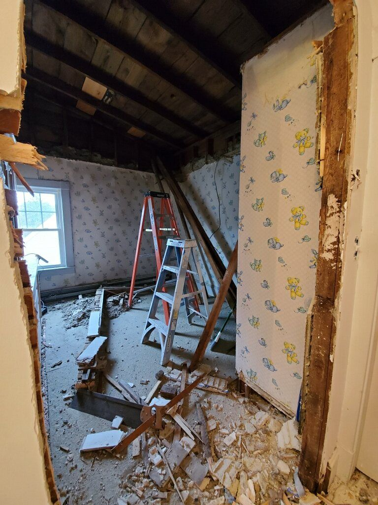 Demo old drywall and lifting ceiling up with a drywall