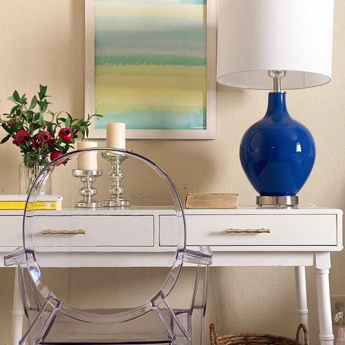 A white desk with faux bamboo details, gourd lamp, lucite chair and serene painting serve as a bedside table and a place to catch up on work and play.