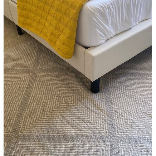 A soft, diamond pattern flatweave rug and textured quilt bring warmth and cozy-ness to the space