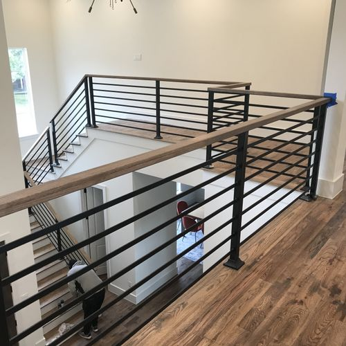 Custom staircase and welded railings @ wood cap stained to match floor, floor scraped with grain,