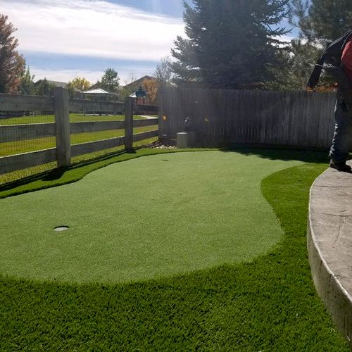 Small synthetic putting green in yard.