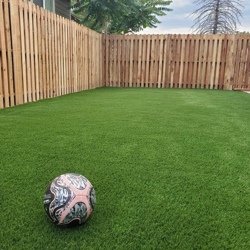 Artificial turf in yard with tall fence installation.