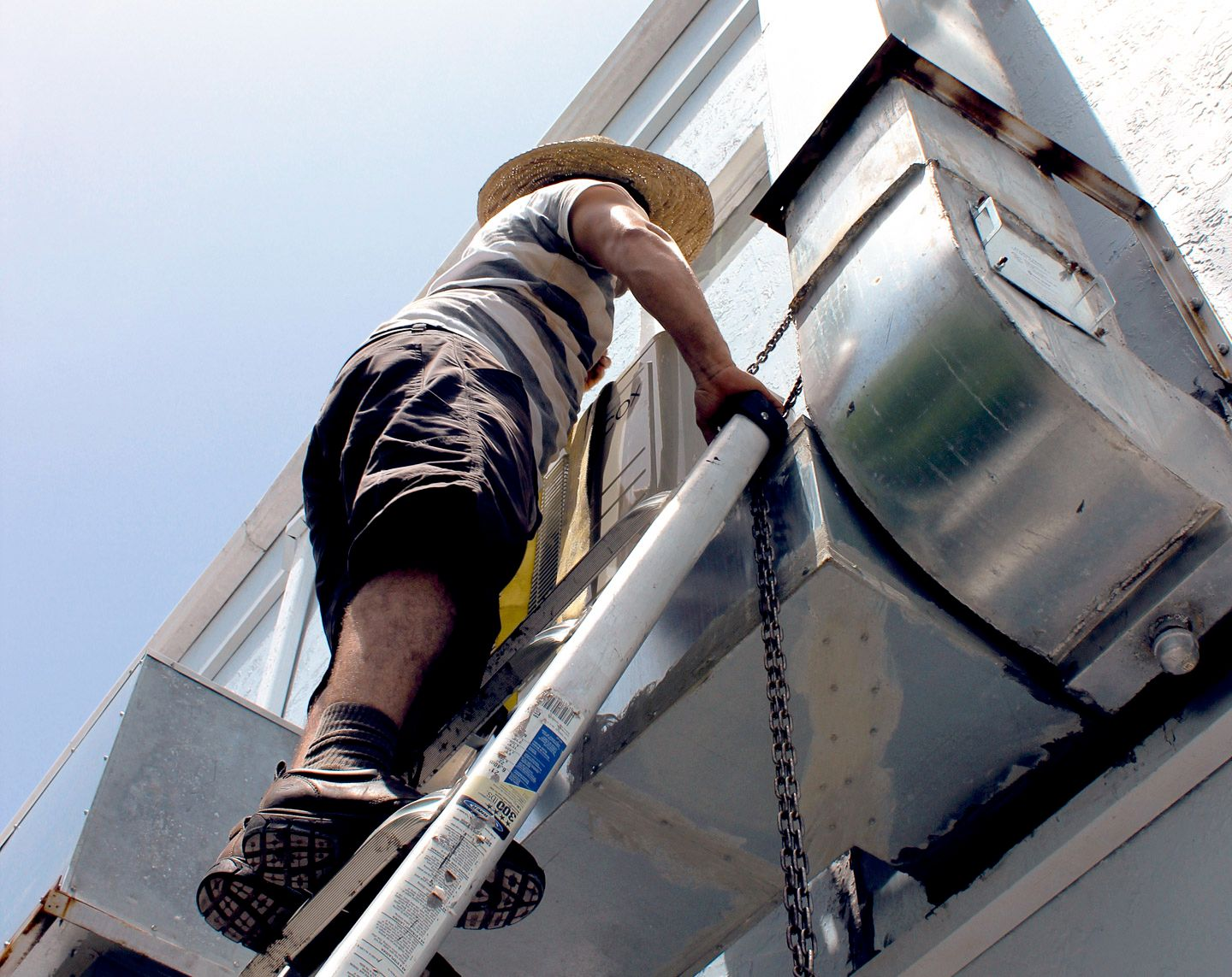 man on ladders fixing HVAC or AC system
