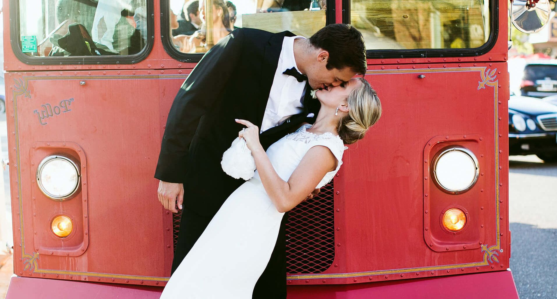 groom and bride kissing in front of bus