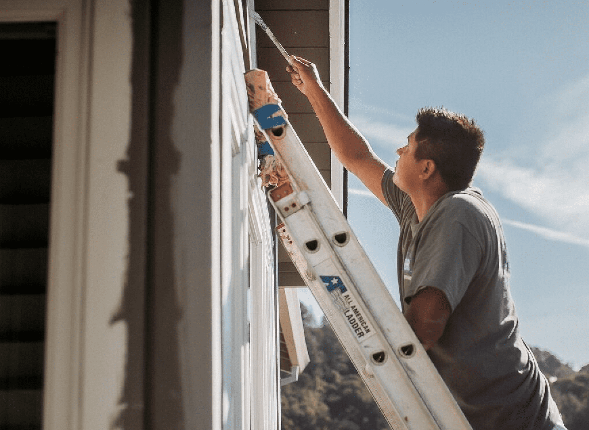 painter on ladder painting house exterior