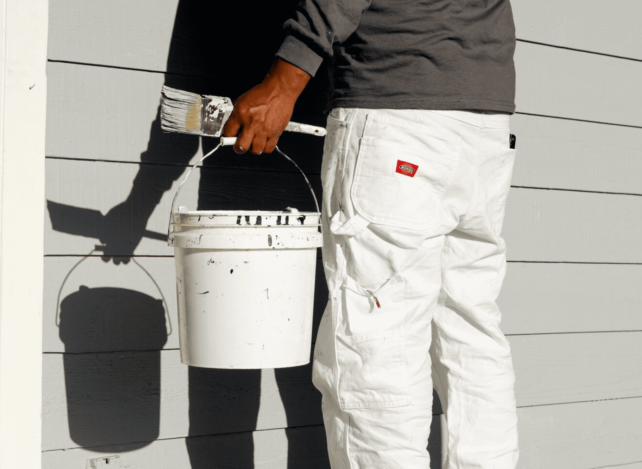 painter holding paint bucket and paint brush