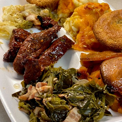 Beef short ribs in a homemade bbq sauce.  Served with Sweet potatoes, baked Mac and Cheese, side of greens, cabbage, & corn bread muffin.